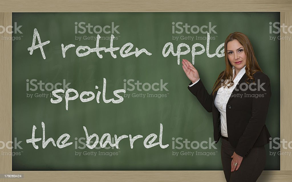 Teacher showing A rotten apple spoils the barrel on blackboard stock photo