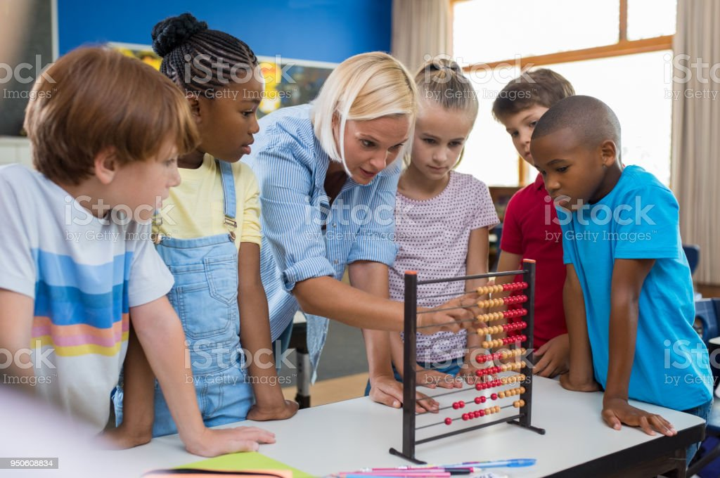 Teacher showing abacus to children stock photo