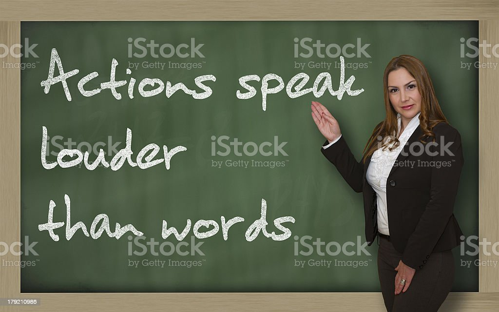 Teacher showing Actions speak louder than words on blackboard stock photo