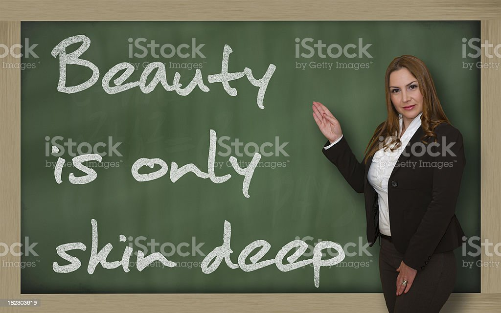 Teacher showing Beauty is only skin deep on blackboard stock photo