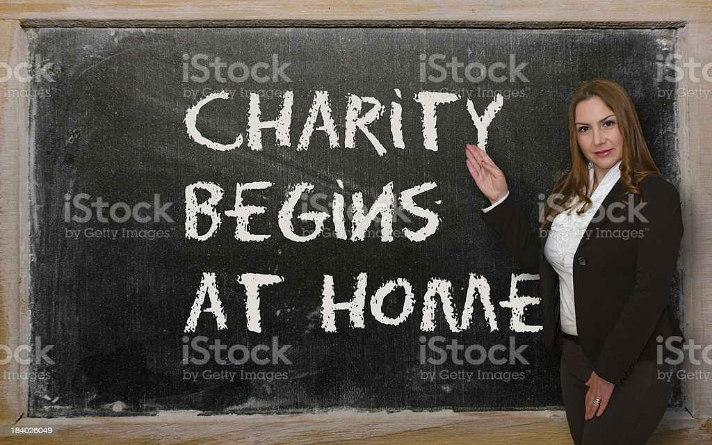 Teacher showing Charity begins at home on blackboard royalty-free stock photo