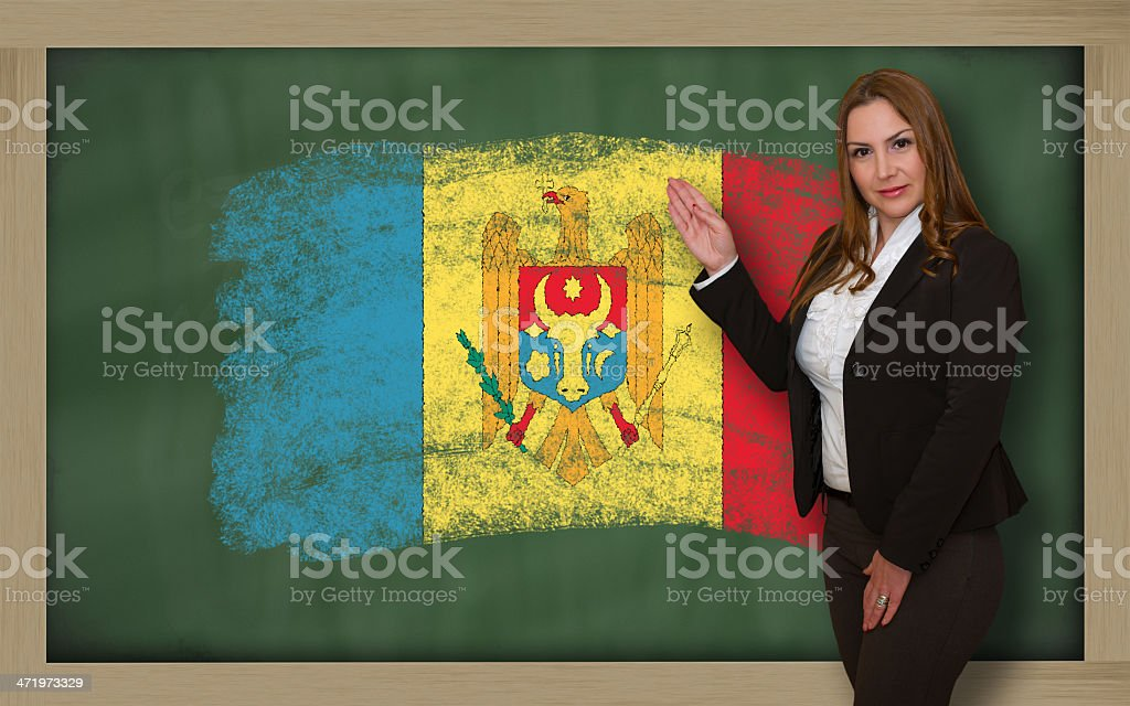 Teacher showing flag of moldova on blackboard for presentation stock photo