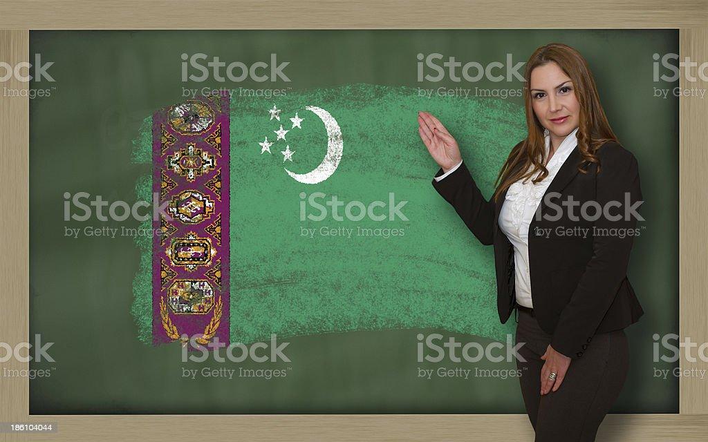Teacher showing flag of turkmenistan on blackboard for presentati stock photo