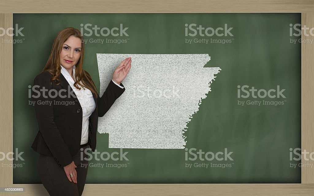 Teacher showing map of arkansas on blackboard stock photo