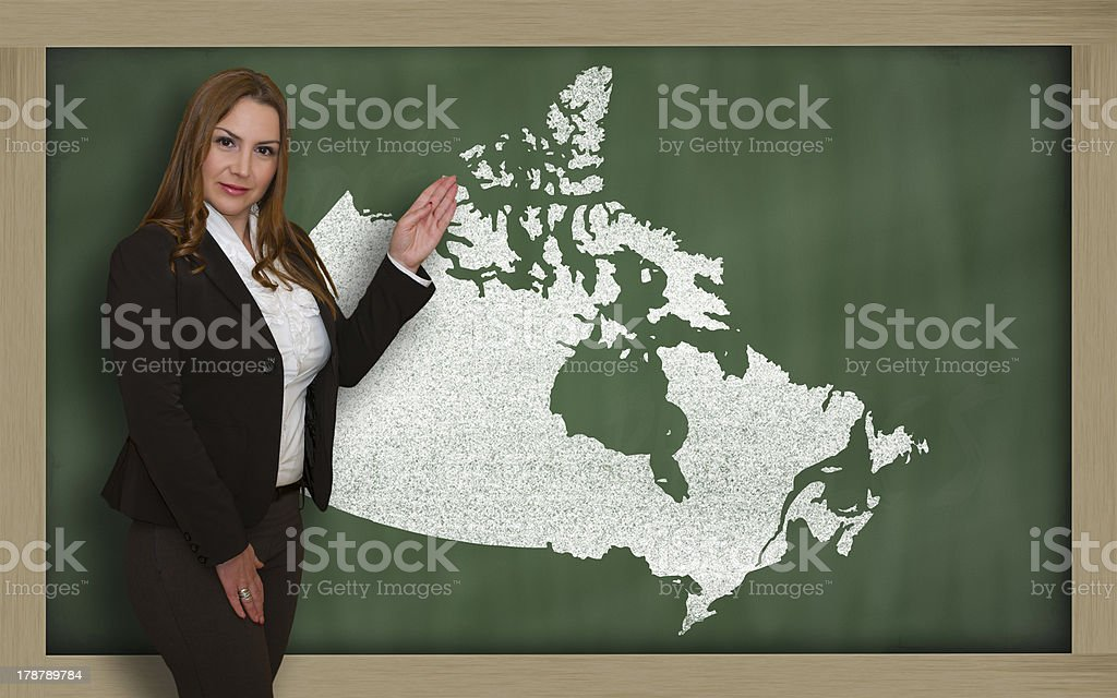 Teacher showing map of canada on blackboard royalty-free stock photo