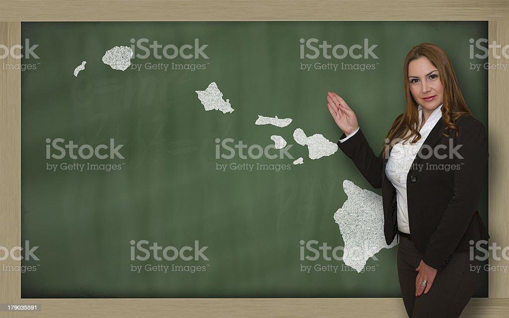 Teacher showing map of hawaii on blackboard royalty-free stock photo