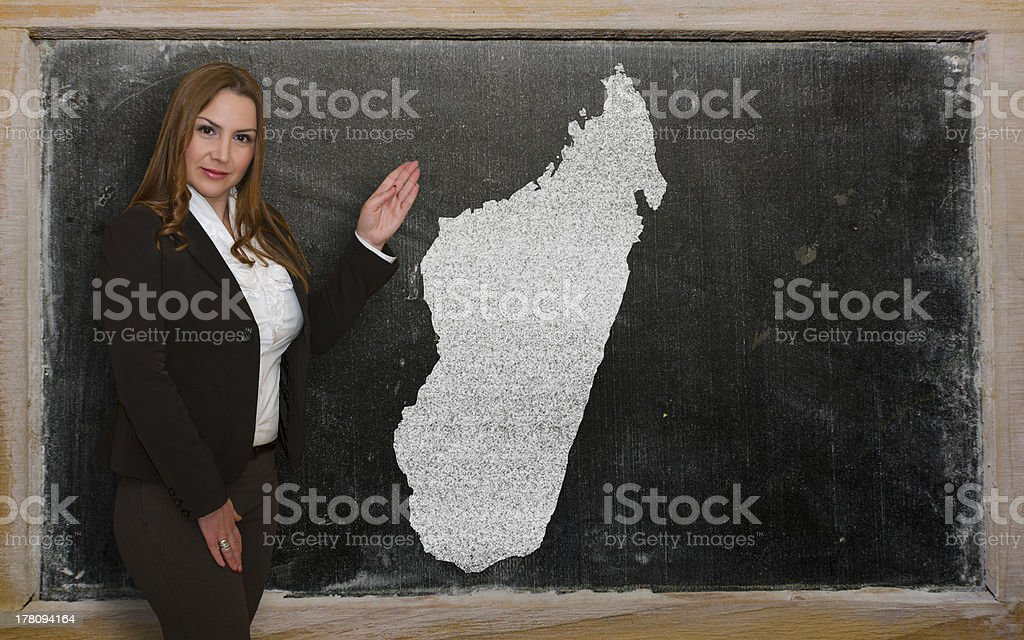 Teacher showing map of madagascar on blackboard royalty-free stock photo
