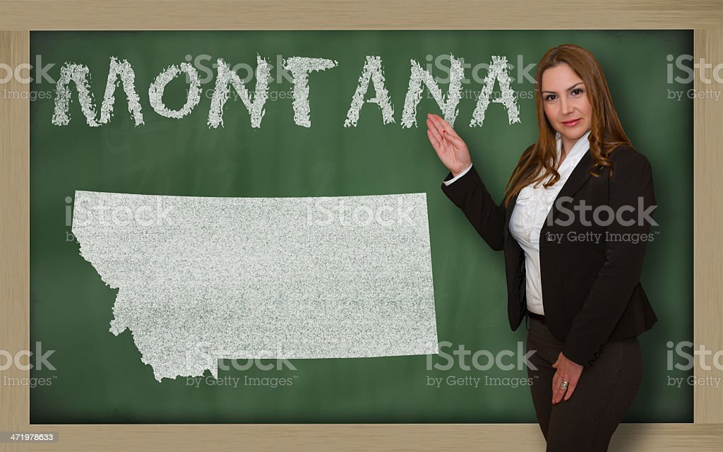 Teacher showing map of montana on blackboard stock photo