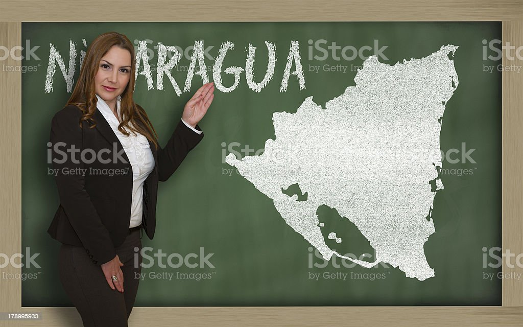 Teacher showing map of nicaragua on blackboard royalty-free stock photo