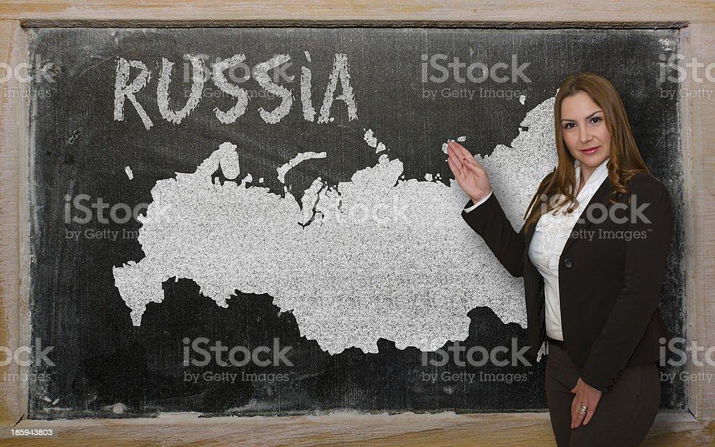 Teacher showing map of russia on blackboard royalty-free stock photo