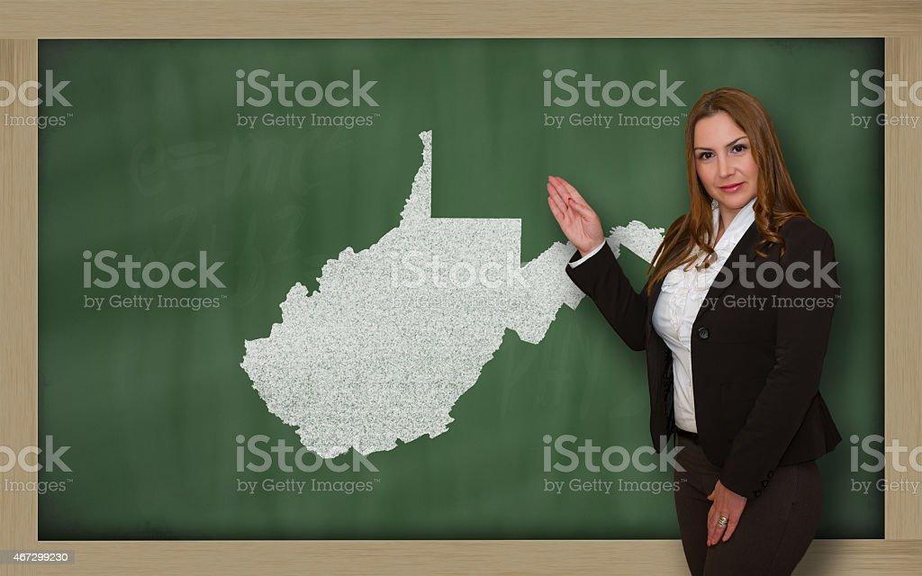 Teacher showing map of west virginia on blackboard stock photo