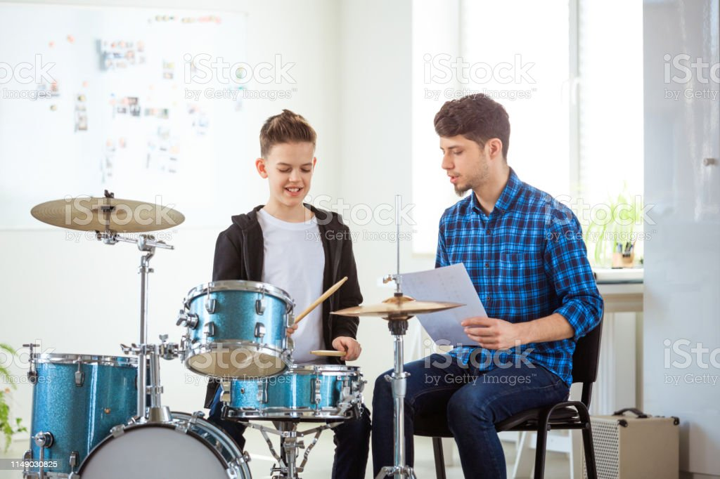 Teacher showing sheet to boy while playing drums Mid adult teacher showing music sheet to pre-adolescent boy. Little drummer is practicing with male instructor. They are sitting in conservatory. 12-13 Years Stock Photo