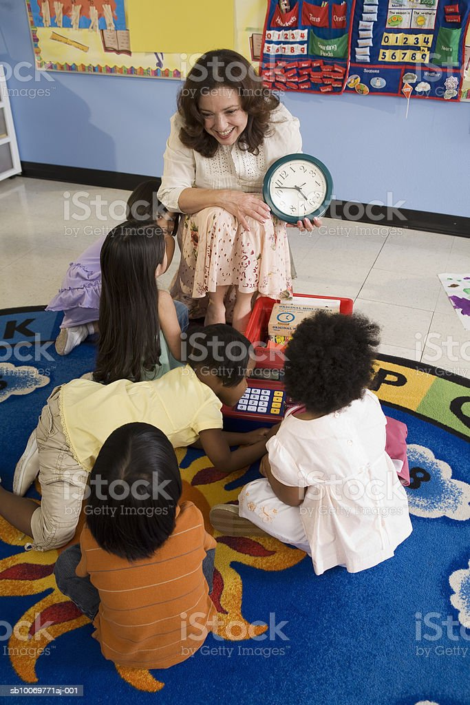 Teacher showing students (2-5) clock in classroom royalty-free stock photo