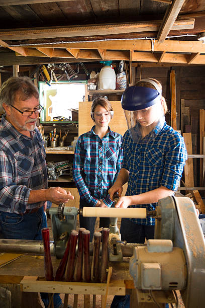 Teacher Showing Students How To Use A Lathe stock photo