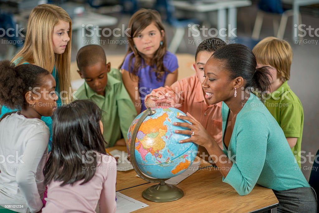Teacher Showing Students Places on a World Globe stock photo