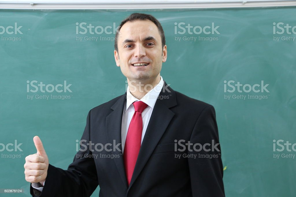 Teacher showing thumbs up sign. stock photo