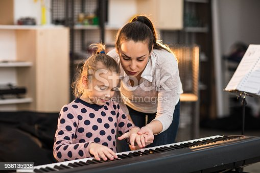 Young woman teaching her child student to play the piano