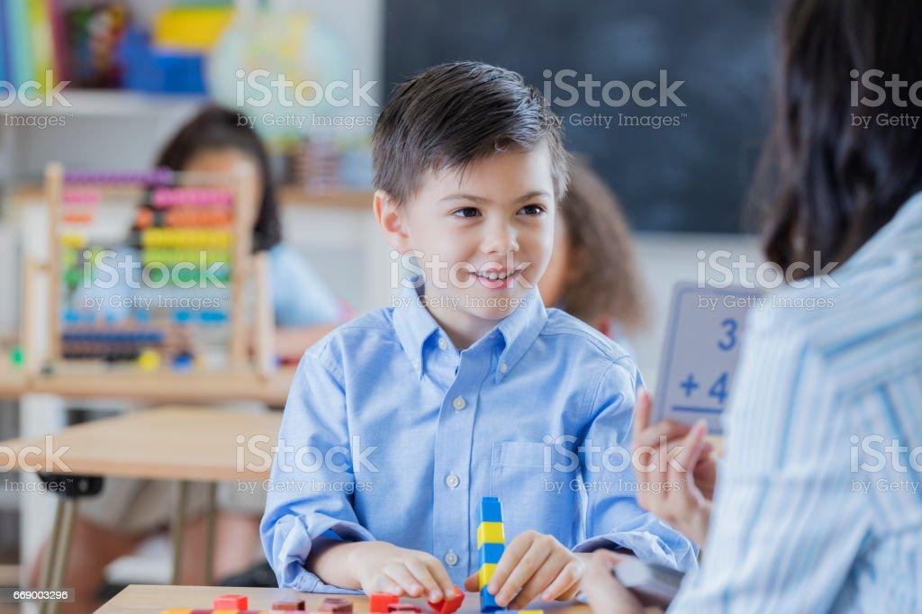 Unrecognizable teacher shows kindergarten schoolboy flashcards.