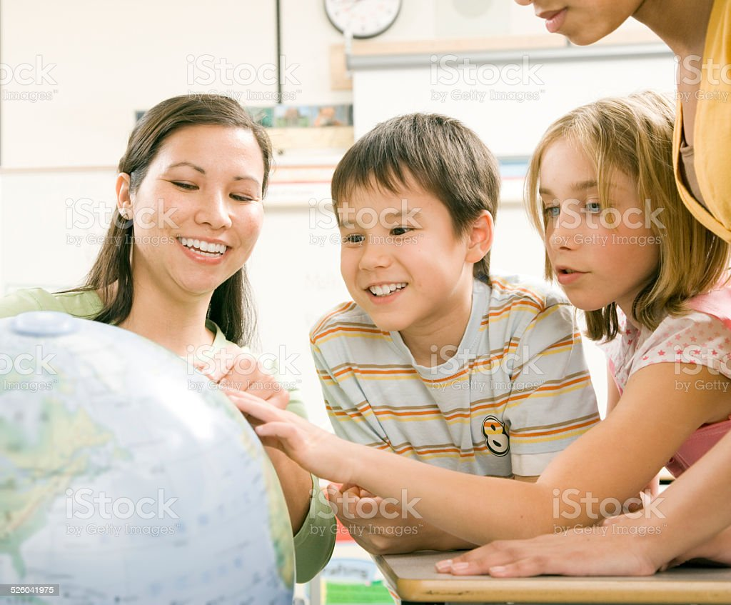 Teacher Shows Young Students A Globe stock photo