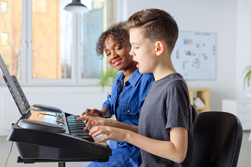 Teacher Singing With Student While Playing Piano Stock Photo - Download Image Now