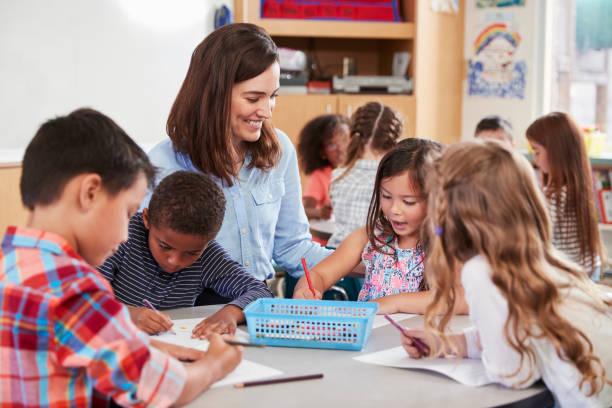 professor sentado na mesa com as crianças da escola jovem lição - professor - fotografias e filmes do acervo