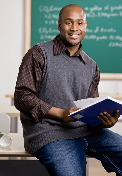 Teacher sitting on desk with text book in school classroom stock photo