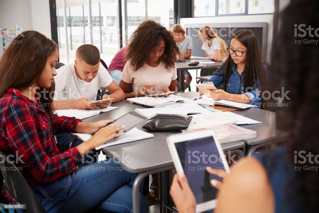 Professor sentado com estudantes do ensino médio usando comprimidos - foto de acervo