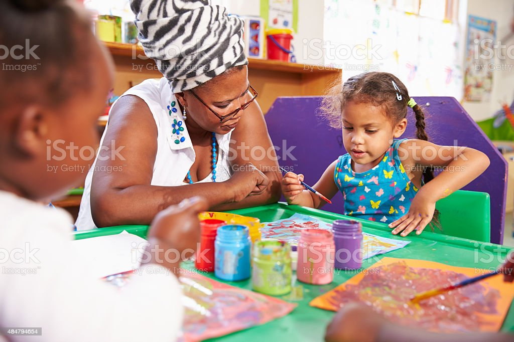 Teacher sitting with kids in a preschool class, close up stock photo