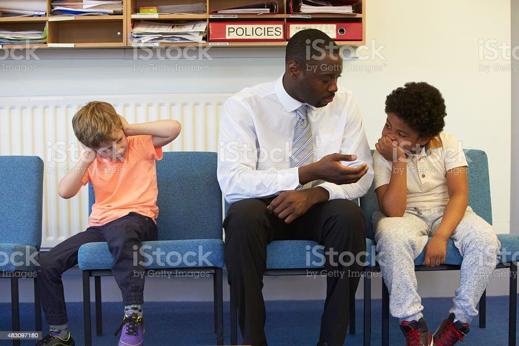 Teacher Solving Problem Between Two School Students stock photo