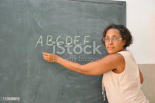 istock Teacher Standing at Classroom Blackboard Writing Alphabets 112035812