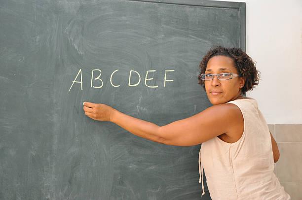 Teacher Standing at Classroom Blackboard Writing Alphabets stock photo