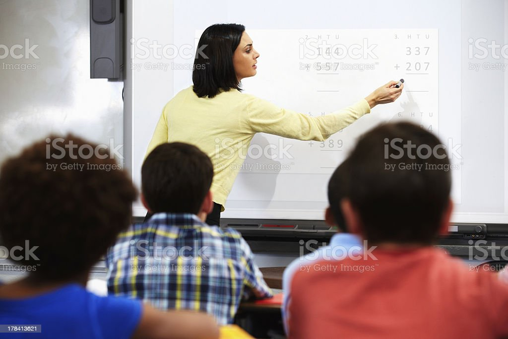 Teacher Standing In Class Using Interactive Whiteboard stock photo