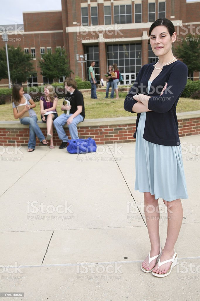 Teacher Standing on School Grounds with Students in the Background royalty-free stock photo