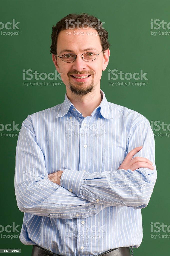A teacher standing with arms crossed while smiling as well  royalty-free stock photo
