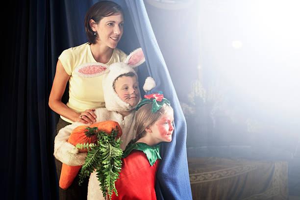 lehrer stehen, kinder (5-7) in kostümen hinter der bühne cu - mädchen vorhänge stock-fotos und bilder