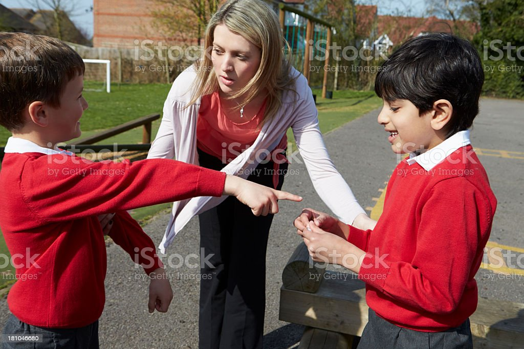 Teacher Stopping Two Boys Fighting In Playground stock photo