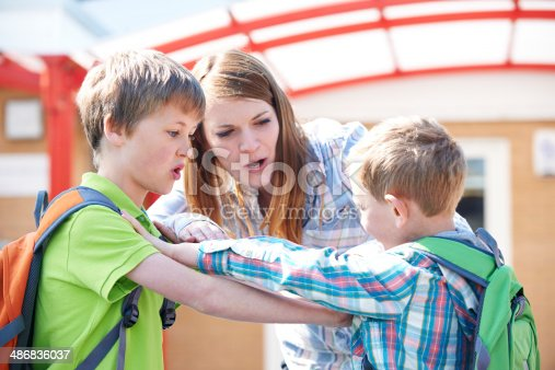 istock Teacher Stopping Two Boys Fighting In Playground 486836037