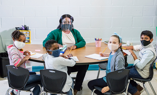 A multi-ethnic group of four children wearing face masks sitting at a table with their elementary school teacher, a mid adult African-American woman in her 30s, wearing a mask and face shield. They have returned to school during the covid-19 pandemic.