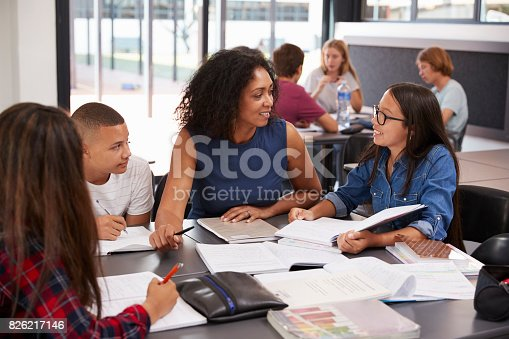 istock Teacher studying school books in class with high school kids 826217146