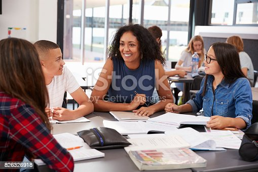 istock Teacher studying school books in class with high school kids 826326918