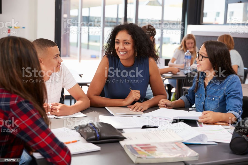 Teacher studying school books in class with high school kids stock photo