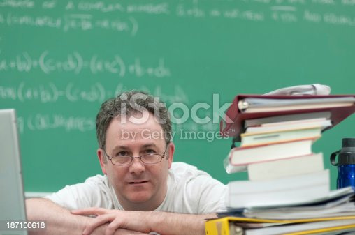 istock Teacher Surrounded by Laptop and Books Looks out at Class 187100618