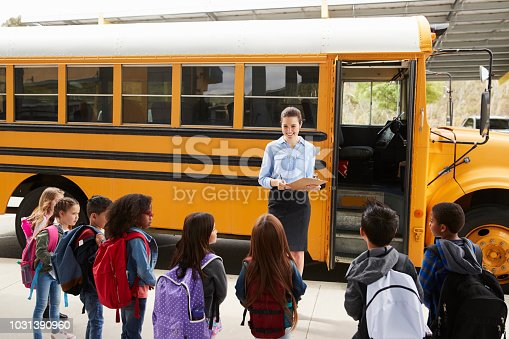 1031397608 istock photo Teacher taking a register of school kids by school bus 1031390960