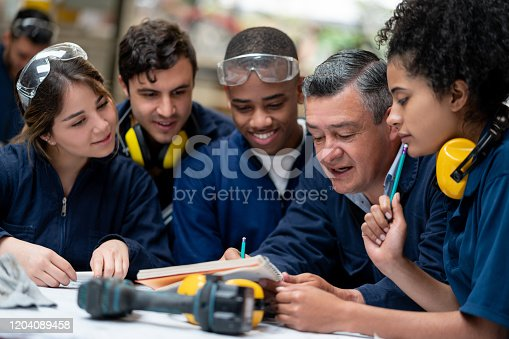 Teacher talking to a group of industrial design students in class and writing notes on his notebook