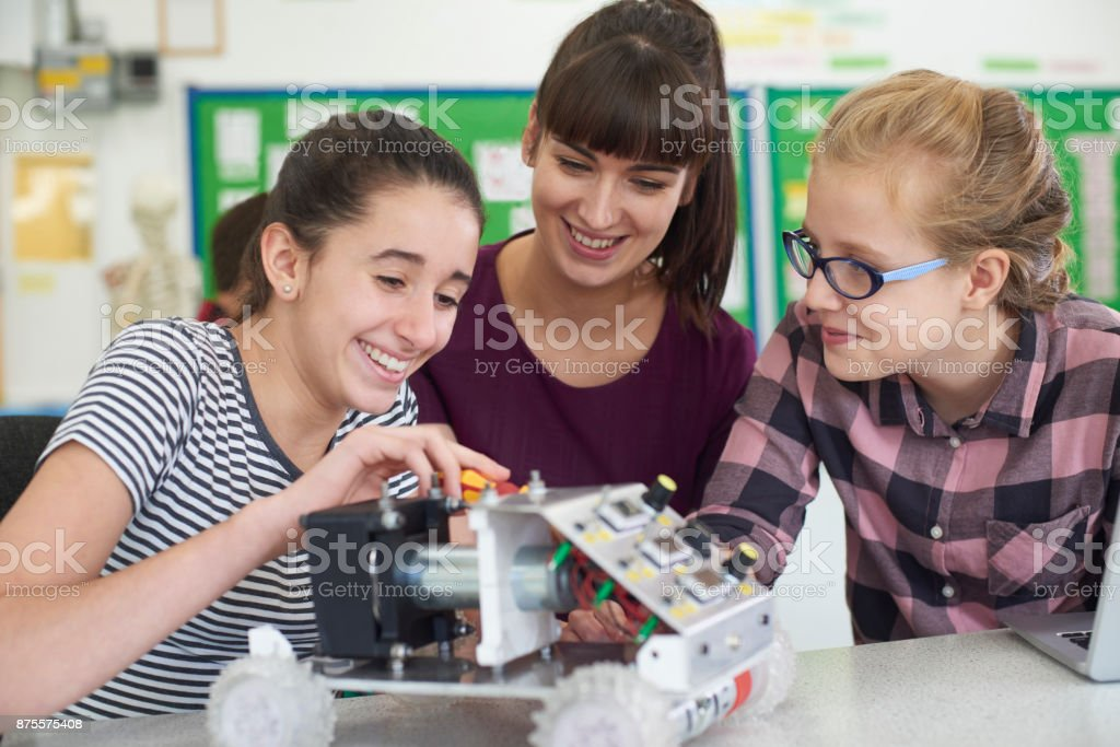 Teacher Talking To Female Pupils Studying Robotics In Science Lesson stock photo