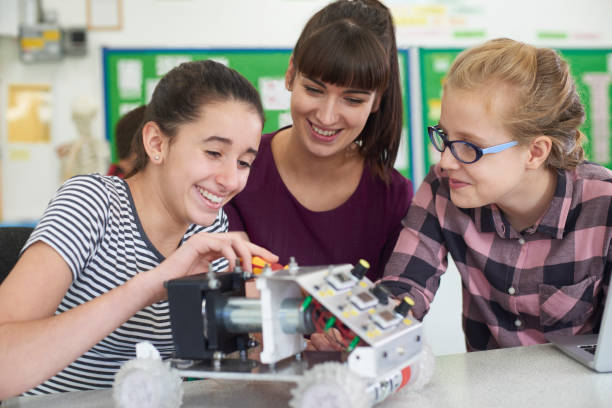 teacher talking to female pupils studying robotics in science lesson - middle school teacher stock pictures, royalty-free photos & images