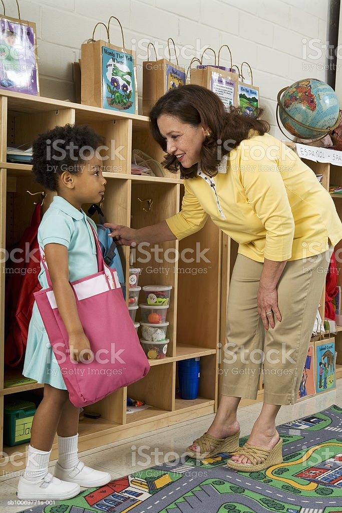 Teacher talking to girl (4-5) in classroom royalty-free stock photo