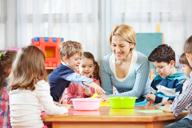Teacher talking with children Young teacher talking with the kids in the kindergarten preschool age stock pictures, royalty-free photos & images