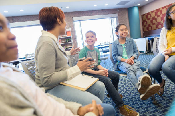 teacher talks with a group of students - school counselor stock photos and pictures