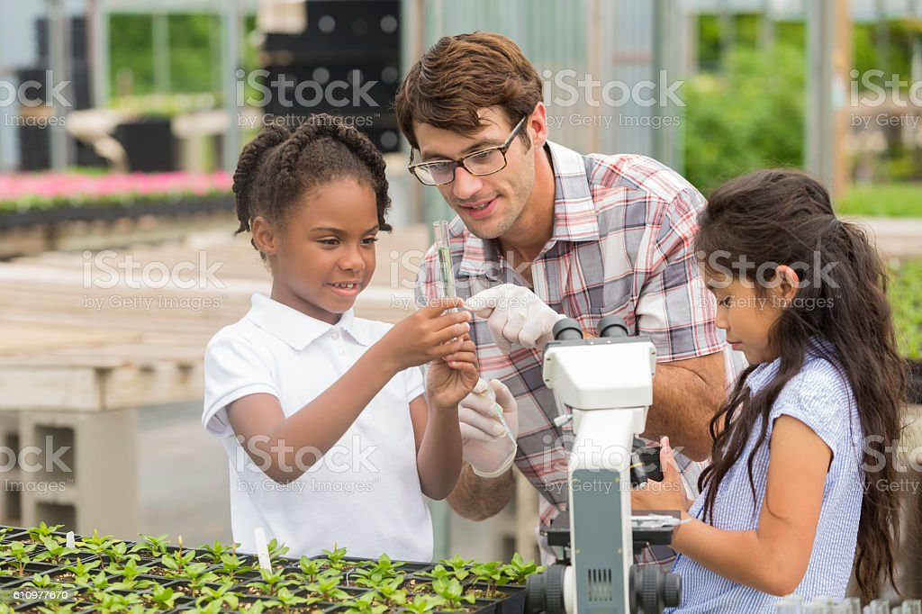Teacher talks with students about plant life during field trip stock photo